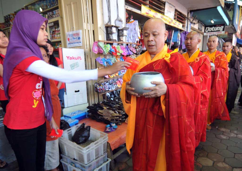 Une employée d'un magasin musulman donne l'aumône à des moines bouddhistes à Magelang, au centre de l'île de Java, le 16 mai 2011, à la veille de la fête de Vesak, qui commémore la naissance, l'illumination et la mort de Bouddha. (Crédit : AFP PHOTO / CLARA PRIMA)